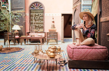 Fotorolgordijn Marokko Traveling by Morocco. Happy young woman in hat relaxing in traditional riad interior in medina.