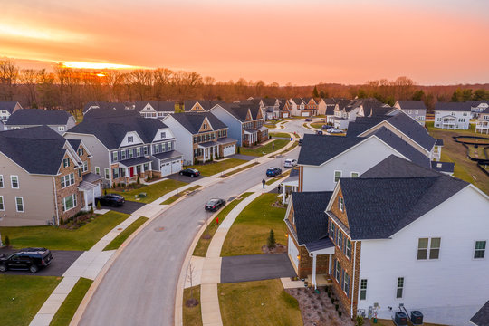 Aerial sunset panorama of luxury real estate development single family house neighborhood curving street with dramatic sky in Maryland USA