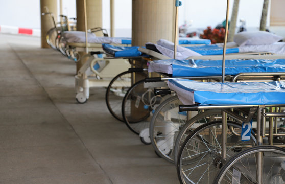 Closeup of wheel-beds and stretchers in front of O.P.D. preparing for emergency medical service.