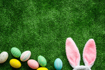 Tuinposter Gras Easter concept. Eggs, Bunny's ears on green grass background top-down copy space
