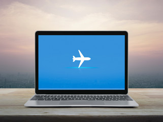 Airplane flat icon with modern laptop computer on wooden table over office city tower and skyscraper at sunset sky, vintage style, Business transportation online concept