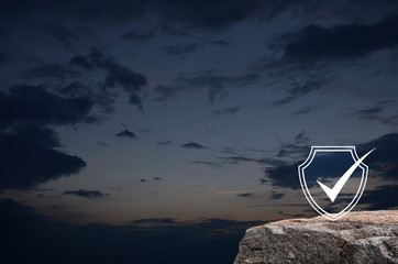 Security shield with check mark flat icon on rock mountain over sunset sky, Technology internet cyber security and anti virus concept