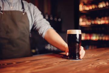 Barman hold dark cold fresh beer to client in pub behind bar. Blur background