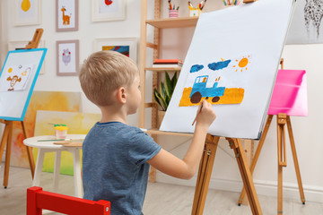 Cute little child painting during lesson in room
