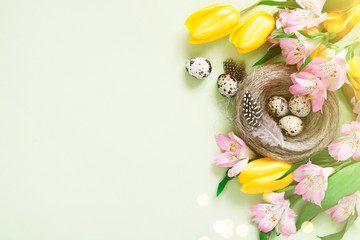 Wall Mural - Easter festive background with quail eggs in the nest decorated with flowers
