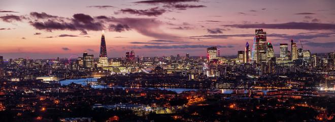 Fotomurales - Weites Panorama der London Skyline am Abend mit rotem Himmel und den beleuchteten Wolkenkratzern der Stadt, Vereinigtes Königreich