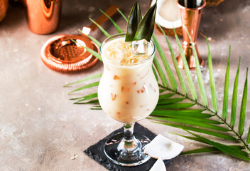 Pina Colada Cocktail on sand beige background with tropical fruits and bar tools, summer relaxation concept, copy space