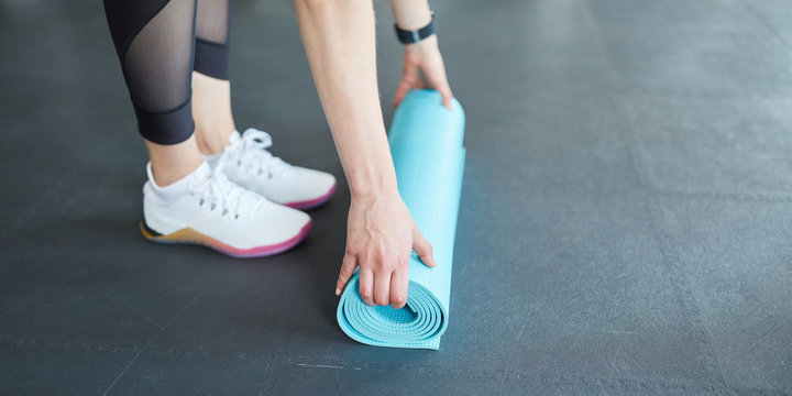 Woman rolls a yoga mat together after workout