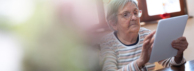 Elderly woman and new technologies; panoramic banner