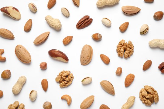 Different delicious nuts on white background, flat lay