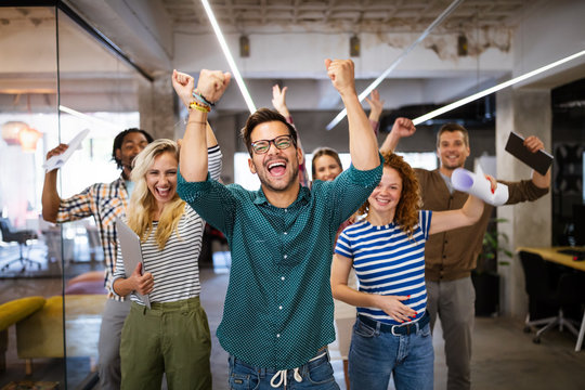 Happy business people celebrating success at company
