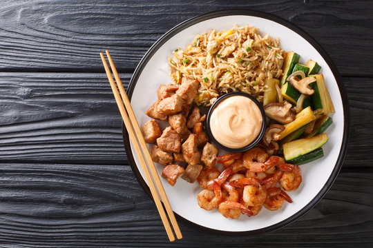 Serving hibachi of rice, shrimp, steak and vegetables served with sauce closeup in a plate. Horizontal top view