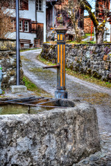 Old fountain from the 18th century in Diesbach, Glarus canton in Switzerland