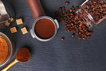 Fotobehang - Coffee filter holder with and roasted beans scattered around on black background