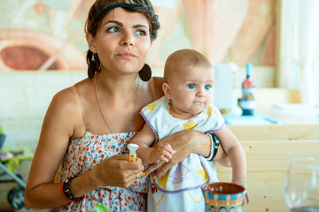 Mom feeds the baby from a spoon. Mom gives the baby puree with a spoon. Child up to a year. First Feeding a Baby with a Spoon