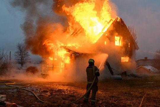 Norwegian firefighter trying to put out flames house on fire