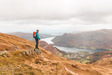 Photographer hiking and looking at panorama on top of mountain