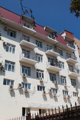 The facade of the building with a white wall, air conditioning, the same windows in the summer resort town.