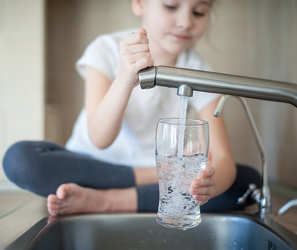 Little girl opens a water tap with her hand holding a transparent glass. Kitchen faucet. Glass of clean water. Filling cup beverage. Pouring fresh drink. Hydration. Healthcare. Healthy lifestyle