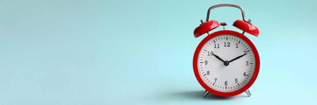 Red alarm clock on turquoise background shows 10 hours 10 minutes in evening or morning. Time to choice concept