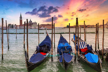 Venetian gondolas at the harbor and San Giorgio Maggiore island at sunset, Venice. Italy