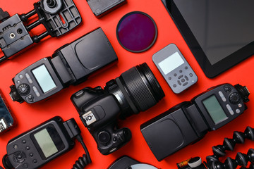 Modern photographer's equipment with tablet computer on color background
