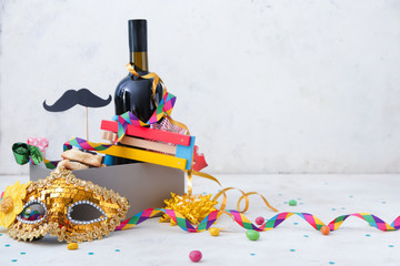 Box with tasty hamantaschen and party decor for Purim holiday on white background