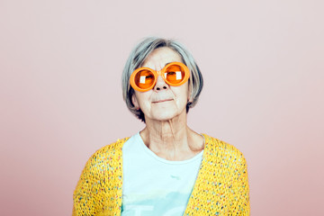 happy elderly grandma portrait with orange sunglasses - forever young lifestyles