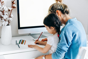 Rear view image of young woman with daughter sitting at home and working. Young mother with toddler child working at the computer and playing. Housewife mother sitting with her child and working.