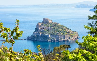 Aerial panoramic view of Aragonese Castle, most popular landmark and travel destination located in Tyrrhenian sea near Ischia island, Italy.