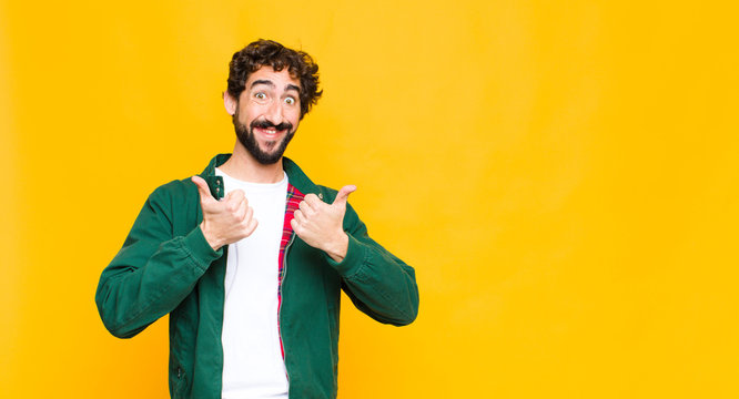 young crazy bearded man smiling broadly looking happy, positive, confident and successful, with both thumbs up against flat wall
