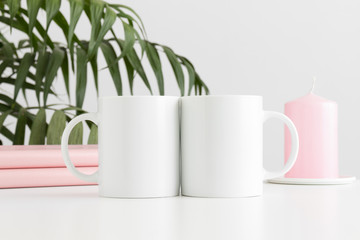 Two mugs mockup with books and a candle on a white table and a palm plant.