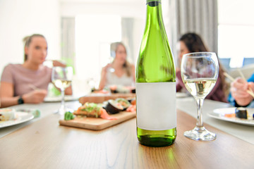Focus on wine with a Group of attractive mature people eating sushi at home