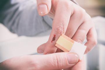 Applying adhesive bandage on finger