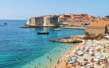 People on beach and Dubrovnik fortress in Adriatic Sea