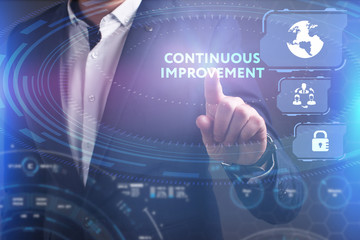 Business, Technology, Internet and network concept. Young businessman working on a virtual screen of the future and sees the inscription: Continuous improvement