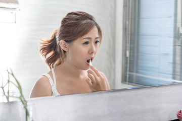 Beautiful young girl brushing teeth in front of her bathroom mirror. Selective focus.