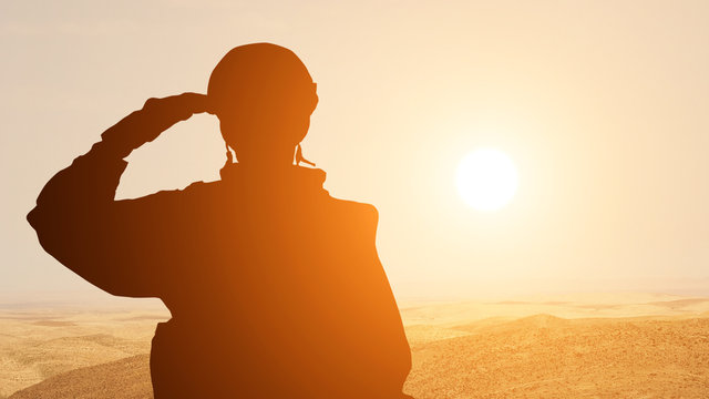 Silhouette Of A Solider Saluting Against the Sunrise in the desert of the Middle East. Concept - armed forces of UAE, Israel, Egypt