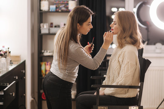 Makeup artist work in beauty studio. Woman applying by professional make up master. Beautiful make up artist make a makeup for blond hair model