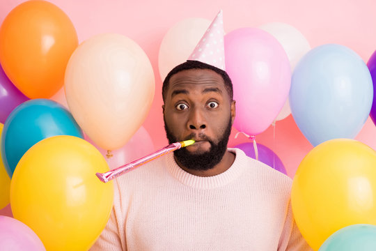 Photo of funky dark skin guy birthday surprise party surrounded many balloons blowing noisemaker crazy guest wear paper cone cap sweater on pink color background