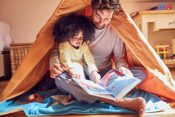Father and daughter reading book in teepee