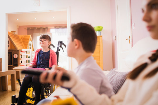 Happy girl in wheelchair with siblings at home