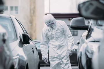 selective focus of asian epidemiologist in hazmat suit and respirator mask inspecting vehicles on parking lot