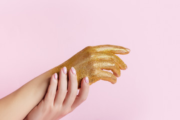 Wall Mural - Perfect manicure with trendy nail art and hand with golden glitter on pink background.