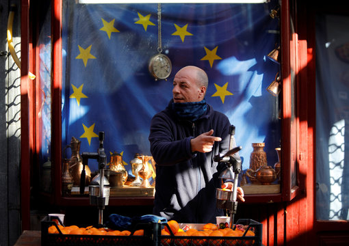 A man squeezes fresh orange juice in front of a EU flag at an old Turkish market in Skopje
