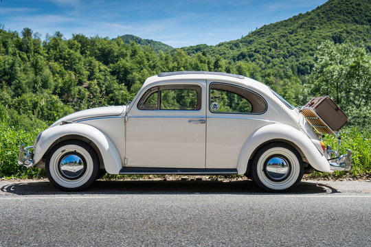Vintage german motor car Beetle parked on a mountain road with woods background. Valsesia / Italy - May 21, 2017.
