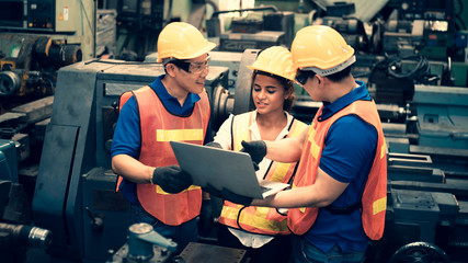 The scene of industrial inspectors team discussing using laptop checking the safety and review function in a metal factory, concept auditor safety, quality control in a factory, quality inspection.
