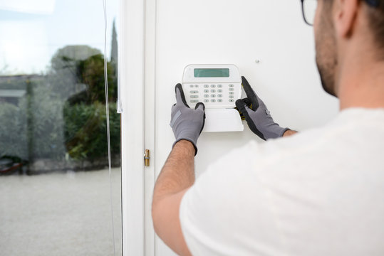 handsome man worker installing alarm technology insurance in home for burglar prevention