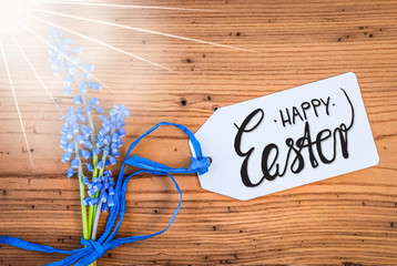 Label With English Calligraphy Happy Easter. Sunny Blue Spring Hyacinth Flower On Rustic Wooden Background.