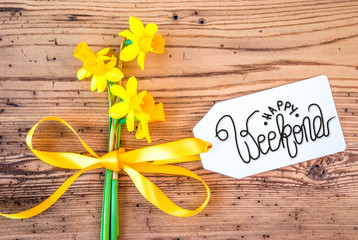 Label With English Calligraphy Happy Weekend. Yellow Spring Narcissus Flower On Rustic Wooden Background.
